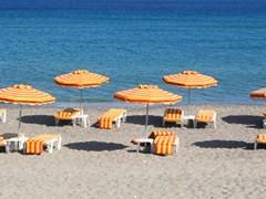 Греция. Остров Кос. Кефалос пляж. Оранжевые стулья и зонтики на пляже